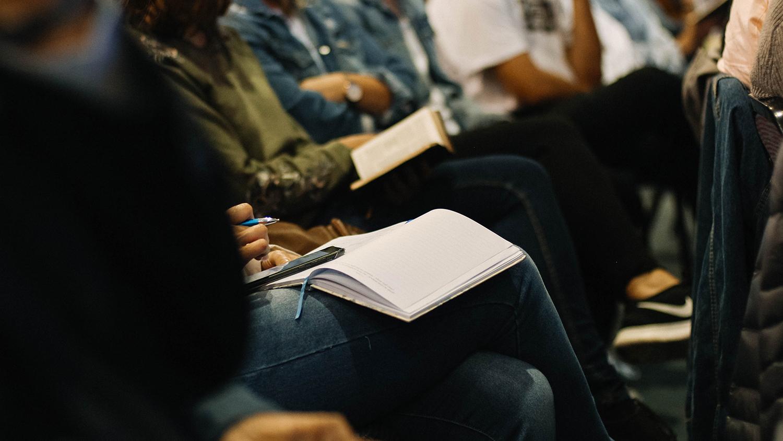 Menschen machen sich Notizen während einer Veranstaltung.
