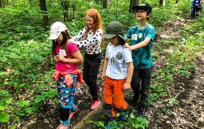 Kinder laufen mit geschlossenen Augen durch den Wald